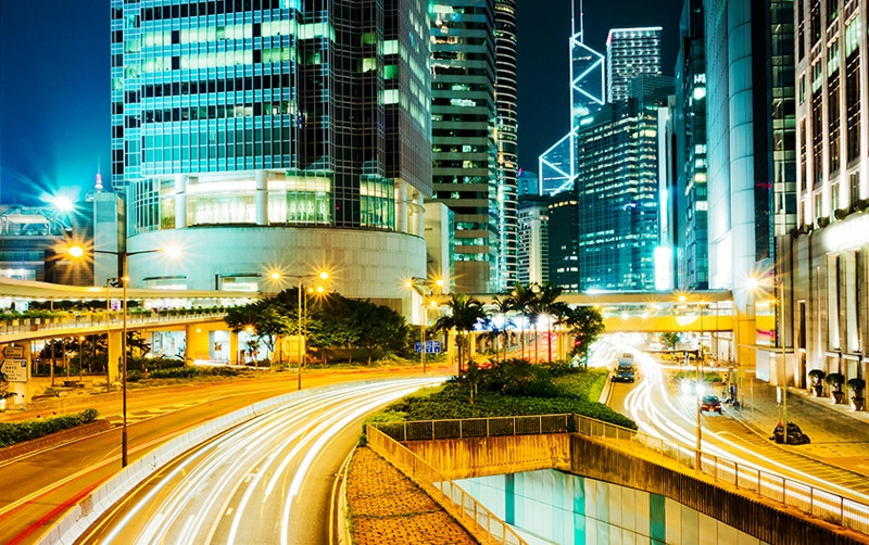Busy city at night with streams of light in streets from cars driving