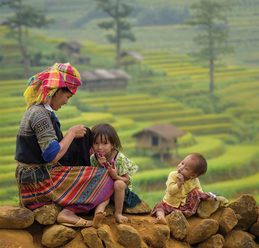 Mother and children sitting atop a wall with fields of crops and a small structure in the background